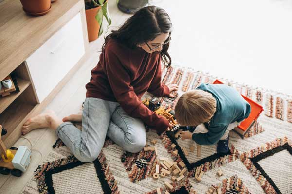 mother playing with son on knitted rug
