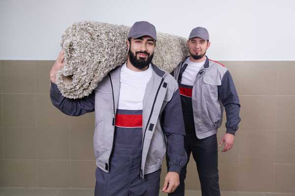 two workers carrying big carpet after washing service